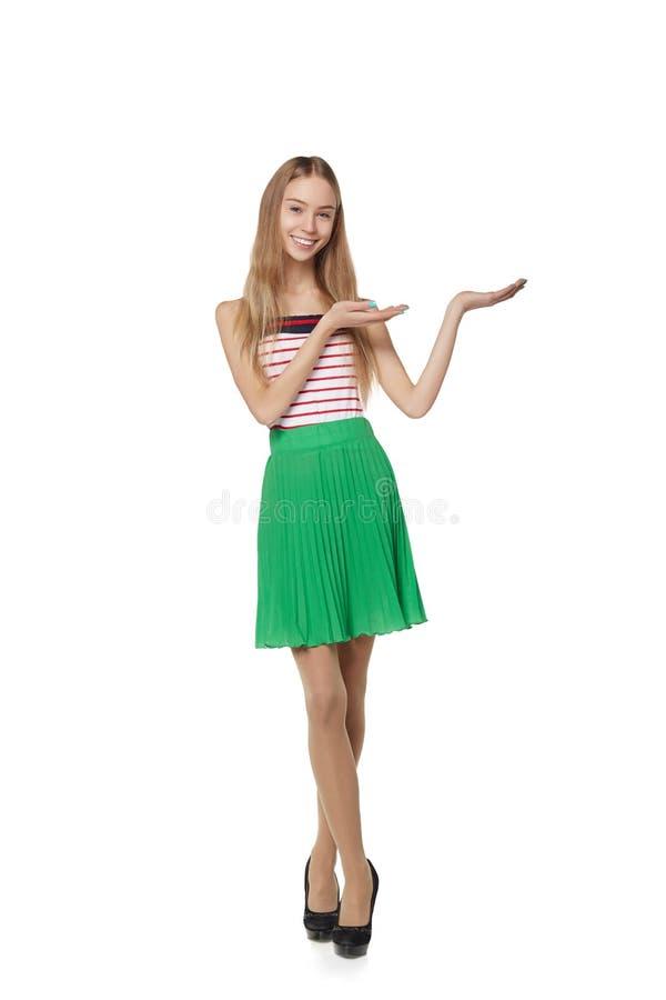 Усмехаясь показ женщины раскрывает ладонь руки с космосом экземпляра для продукта стоковое фото