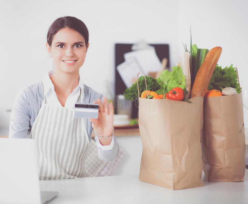 Усмехаясь покупки женщины онлайн используя компьютер и кредитную карточку в кухне стоковое фото