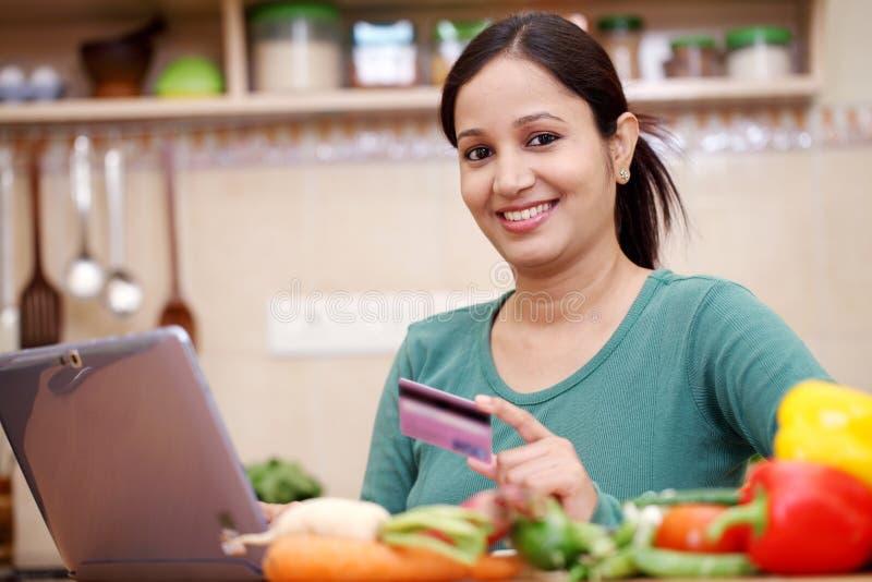 Усмехаясь покупки молодой женщины онлайн стоковое изображение