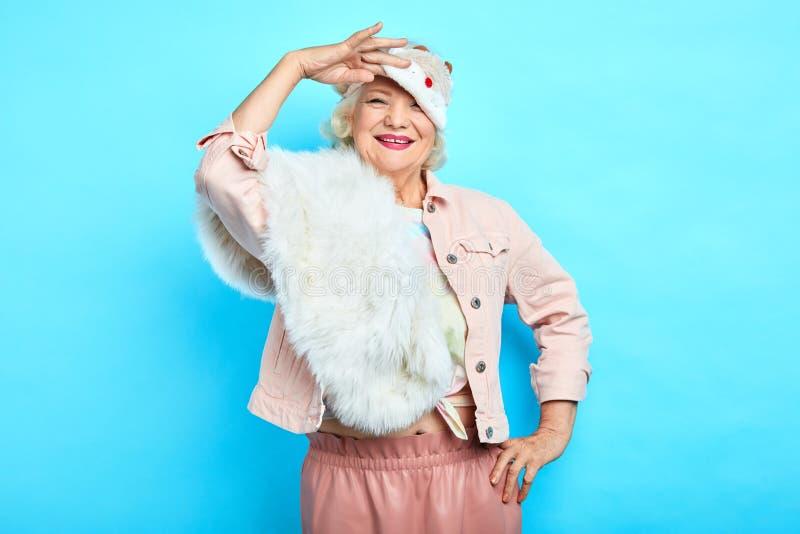 Усмехаясь положительная женщина моды принимая маску стоковое фото