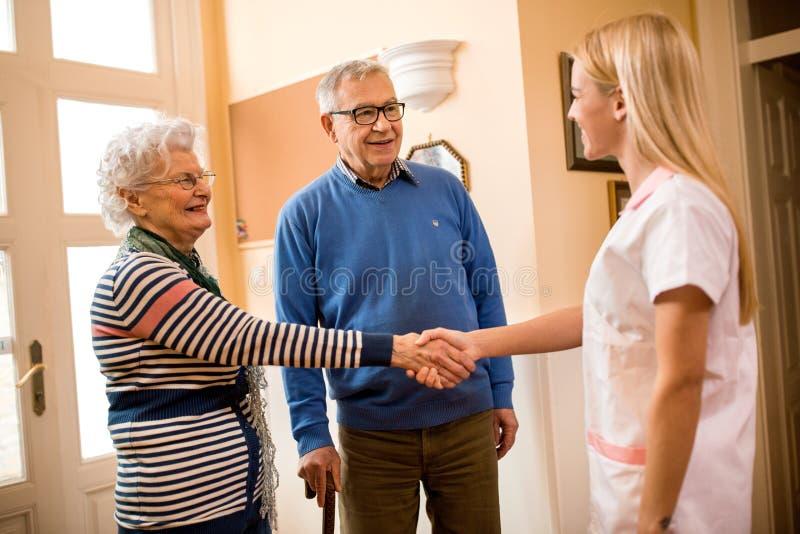 Усмехаясь положительная медсестра трясет руки с новыми пациентами на клинике стоковое фото rf