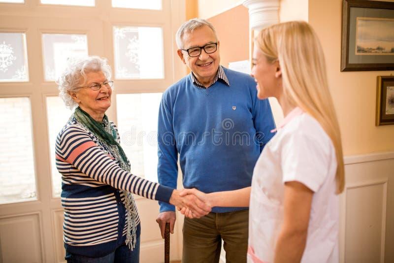 Усмехаясь положительная медсестра трясет руки с новыми пациентами на клинике стоковое фото