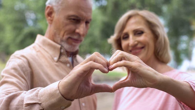 Усмехаясь постаретые пары показывая сердце подписывают, символ влюбленности, счастливое замужество, привязанность стоковое фото