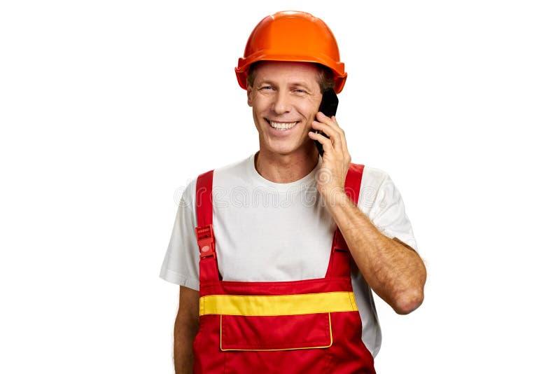 Усмехаясь построитель говоря на сотовом телефоне стоковая фотография rf