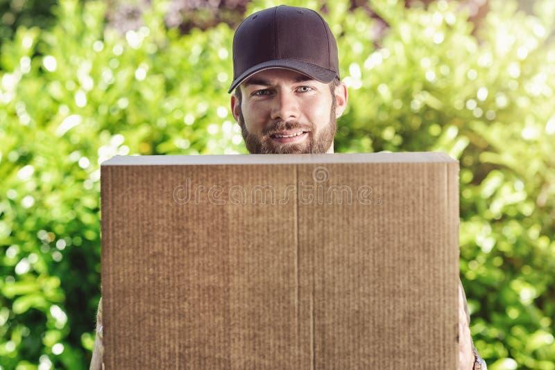 Усмехаясь почтальон нося большой пакет стоковое изображение rf