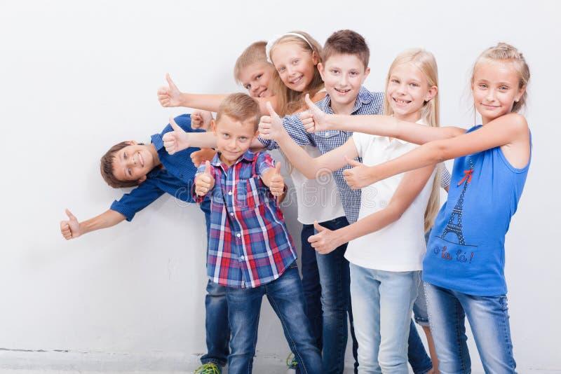 Усмехаясь подростки показывая одобренный знак на белизне стоковые фотографии rf
