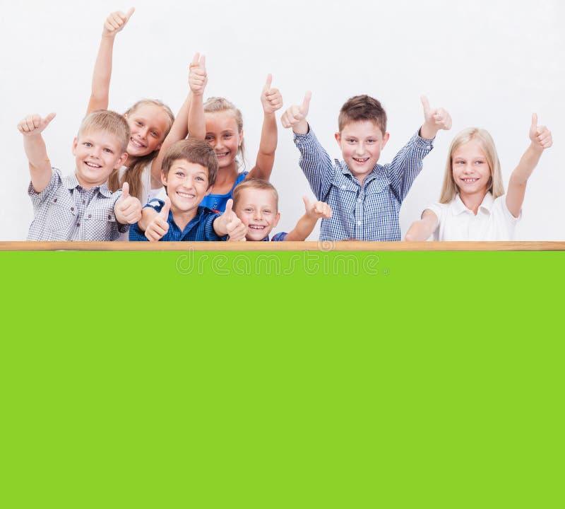 Усмехаясь подростки показывая одобренный знак на белизне стоковое изображение