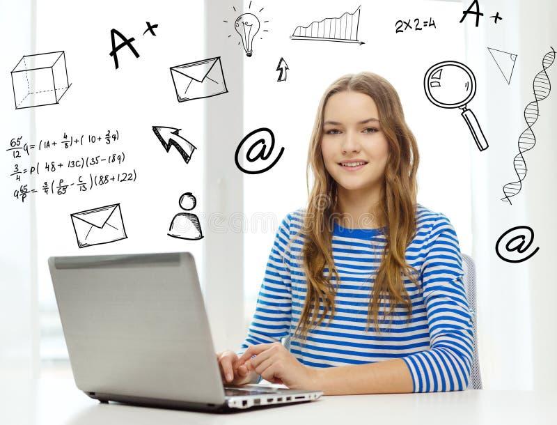 Усмехаясь подростковое gitl с портативным компьютером дома стоковые изображения