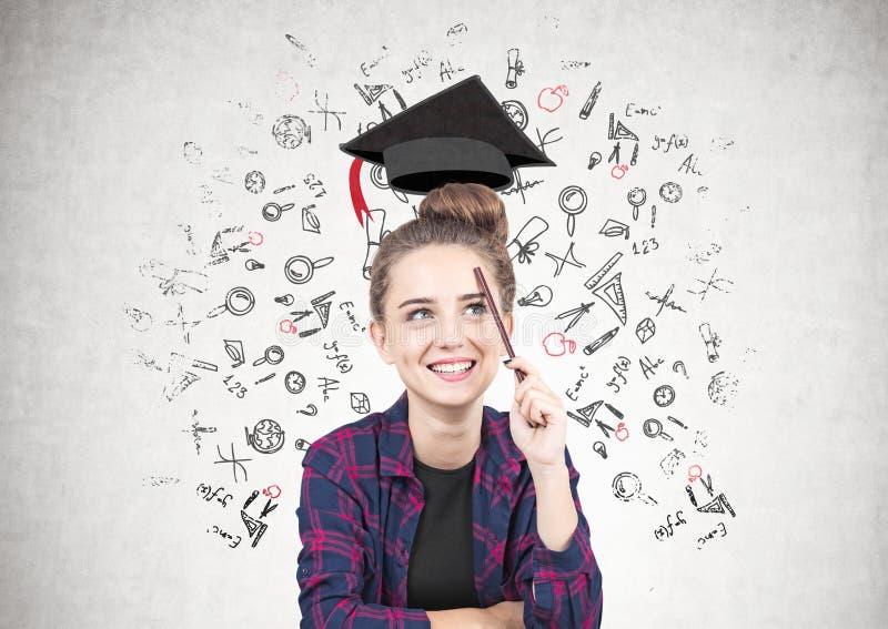 Усмехаясь предназначенная для подростков девушка думая, образование стоковое изображение