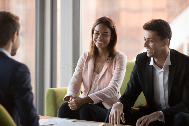 Усмехаясь предприниматели обсуждают в офисе в положительной атмосфере стоковое фото rf