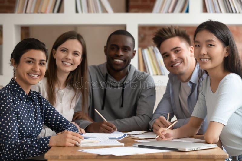 Усмехаясь представлять multiracial groupmates усмехаясь для изображения стоковые фотографии rf