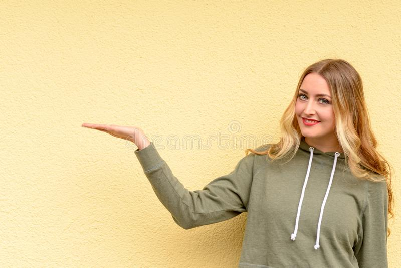 Усмехаясь привлекательная белокурая женщина держа вне руку стоковые изображения
