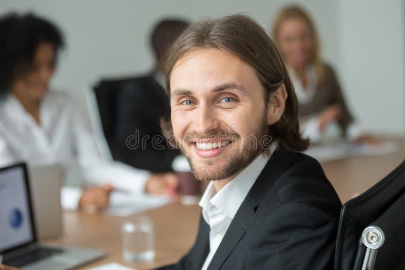 Усмехаясь привлекательный молодой бизнесмен в костюме смотря камеру, стоковое фото
