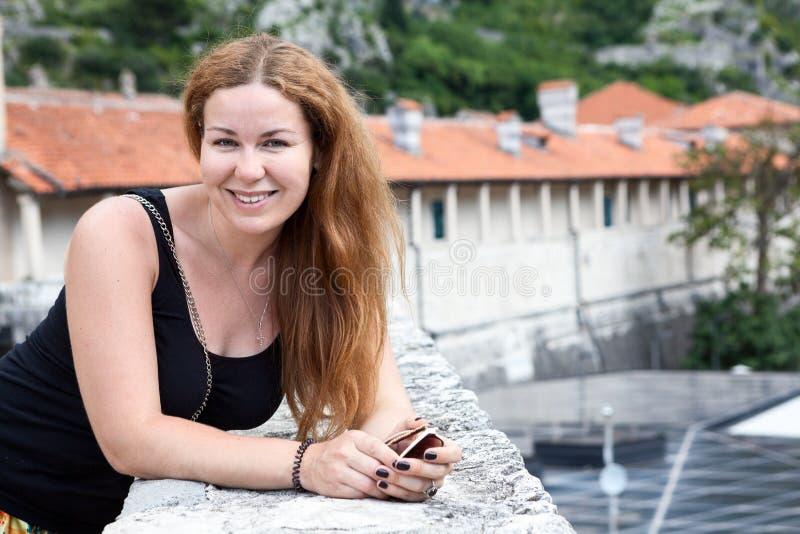 Усмехаясь привлекательный портрет женщины смотря камеру, длинные волосы, черную рубашку, космос экземпляра стоковое изображение rf