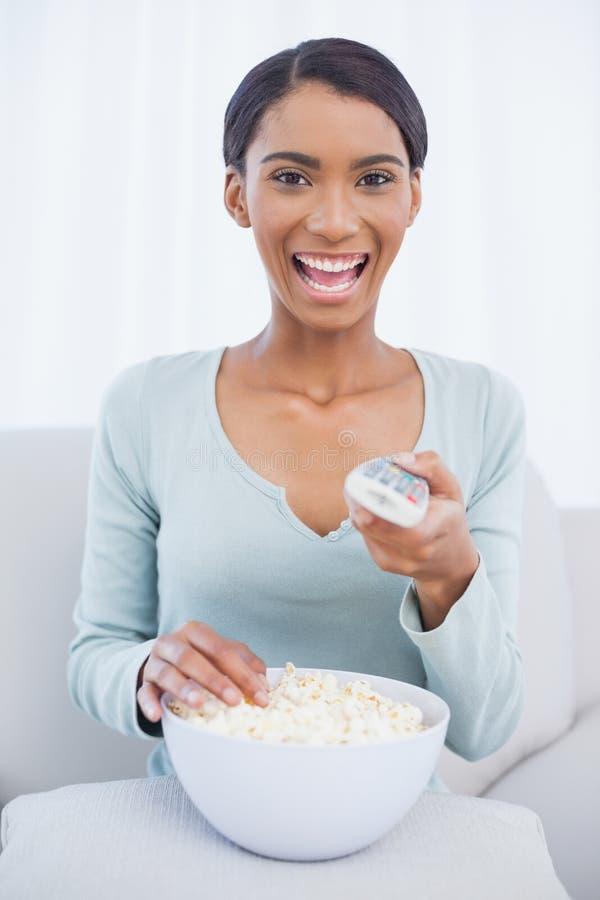 Download Усмехаясь привлекательная женщина есть попкорн пока смотрящ Tv Стоковое Фото - изображение насчитывающей салон, персона: 33739546