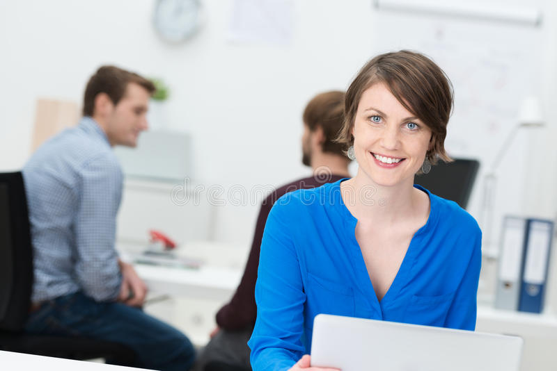 Усмехаясь привлекательная коммерсантка в офисе стоковое фото rf