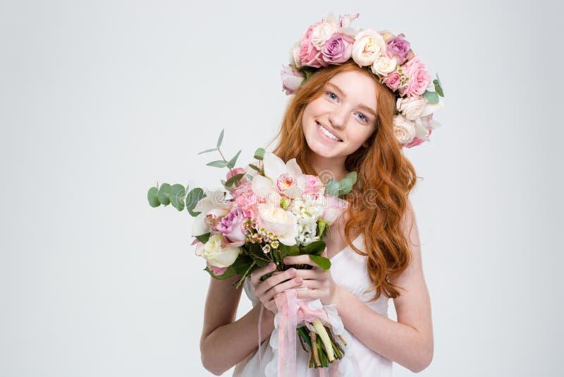 Усмехаясь привлекательная молодая женщина в венке держа букет цветков стоковая фотография rf