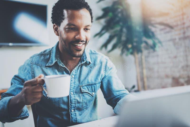 Усмехаясь привлекательный африканский человек делая видео- переговор через цифровую таблетку с деловыми партнерами пока сидящ вну стоковые фото