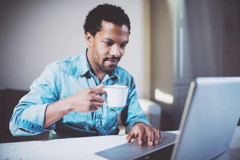 Усмехаясь привлекательный африканский человек делая видео- переговор через компьтер-книжку с партнерами пока выпивающ чай белой ч стоковая фотография