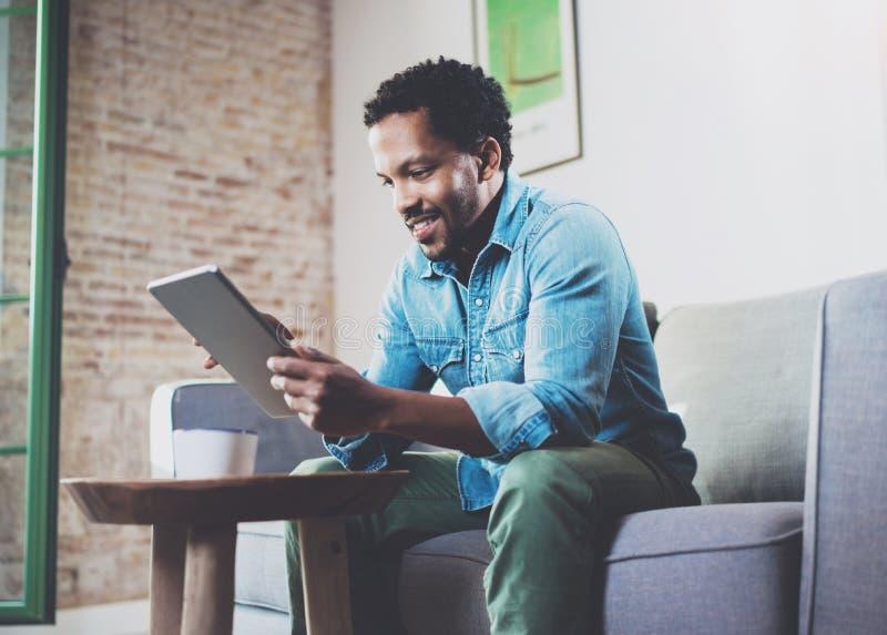 Усмехаясь привлекательный бородатый африканский человек работая дома пока сидящ на софе Используя цифровую таблетку для видео стоковые фото