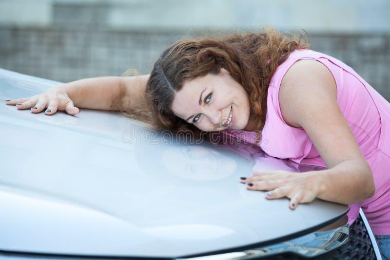 Усмехаясь привлекательный клобук автомобиля обнимать женщины с руками стоковое изображение rf