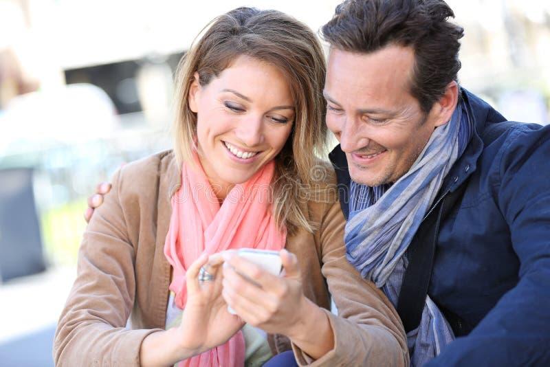 Усмехаясь причудливые пары в городке используя smartphone стоковые изображения rf