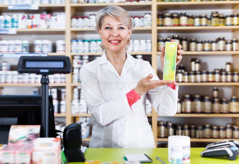 Усмехаясь продукты заботы кожи женщины рекомендуя стоковое фото