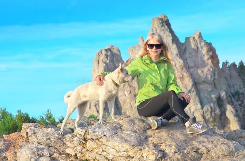Усмехаясь путешественник женщины и белая собака сидя на камнях ослабляя с утесистой горой стоковая фотография rf
