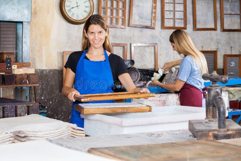 Усмехаясь работники делая бумаги в фабрике стоковое фото rf