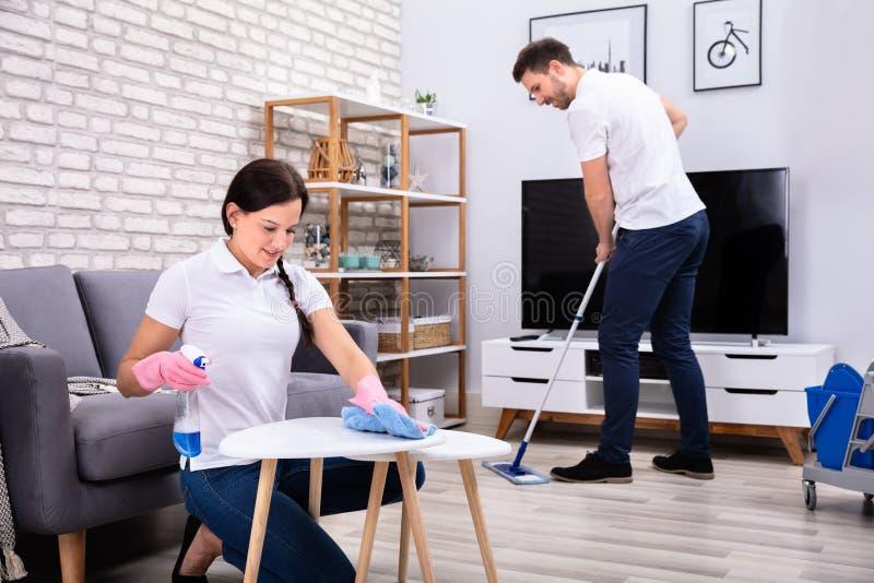 Усмехаясь работники убирая комната стоковое фото rf