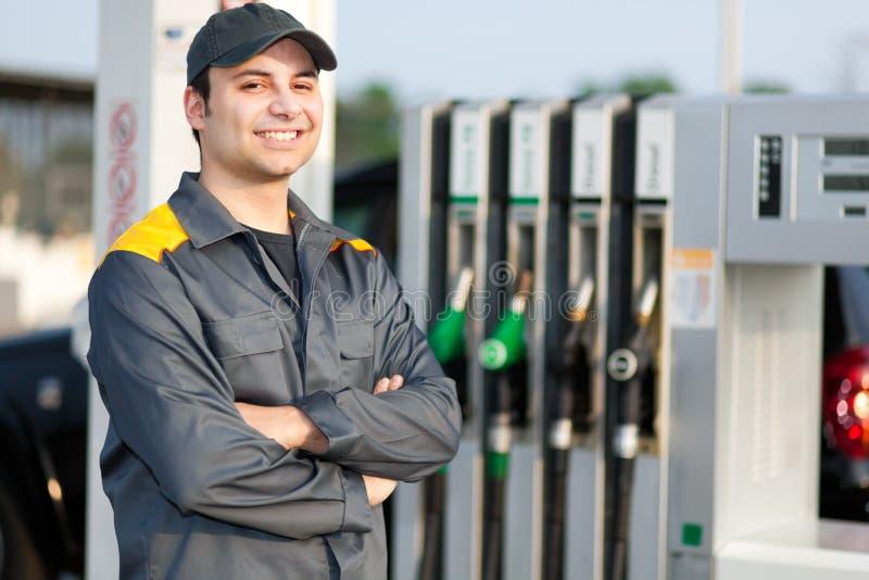 Усмехаясь работник бензоколонки на работе стоковые фотографии rf