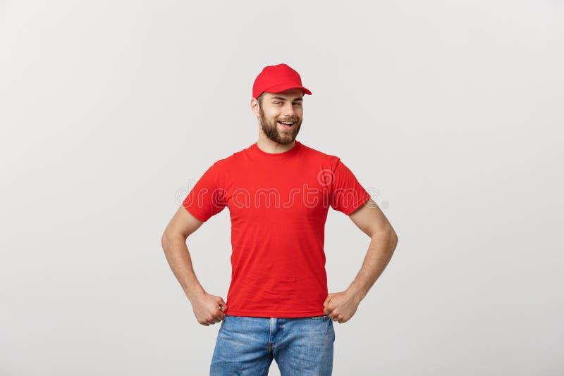 Усмехаясь работник доставляющий покупки на дом в красной форме стоя с рукой пересек - изолированный на белой предпосылке стоковое изображение