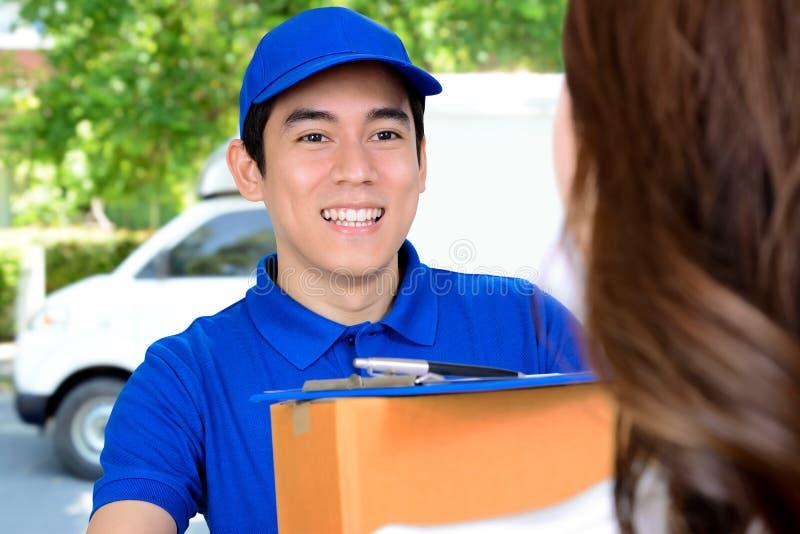 Усмехаясь работник доставляющий покупки на дом поставляя пакет стоковое изображение rf
