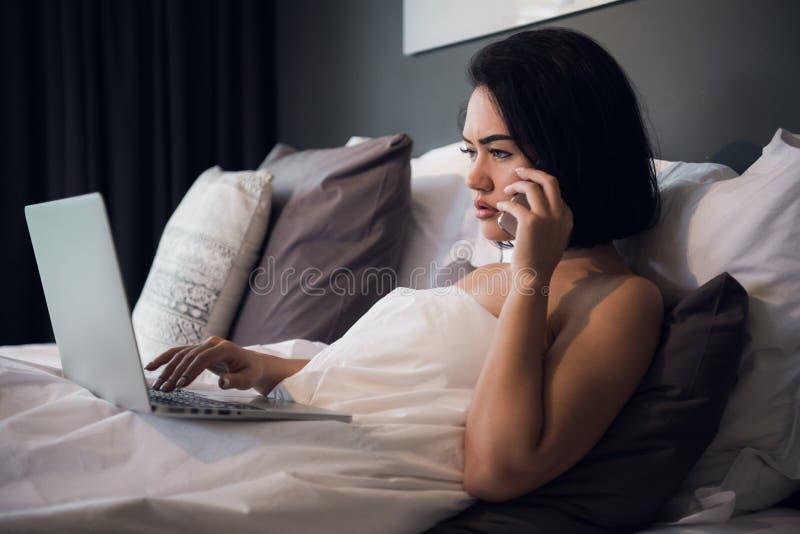 Усмехаясь расслабленная молодая женщина используя мобильный телефон и компьтер-книжку в кровати дома стоковое фото rf