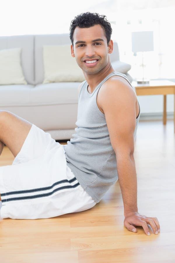 Усмехаясь расслабленный молодой человек сидя на поле в живущей комнате стоковая фотография rf