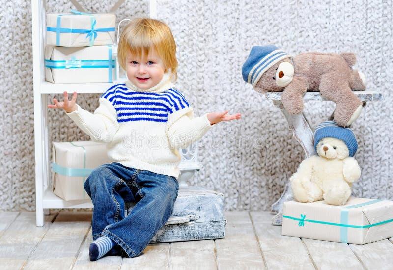 Усмехаясь ребенк с подарочными коробками и плюшевыми медвежоатами стоковое фото rf