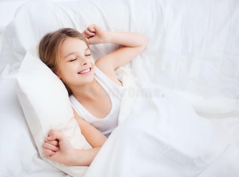 Усмехаясь ребенок девушки просыпая вверх в кровати дома стоковая фотография
