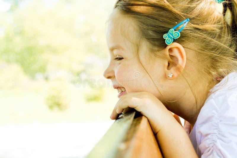 Усмехаясь ребенок девушки рассматривает перила стоковые фотографии rf