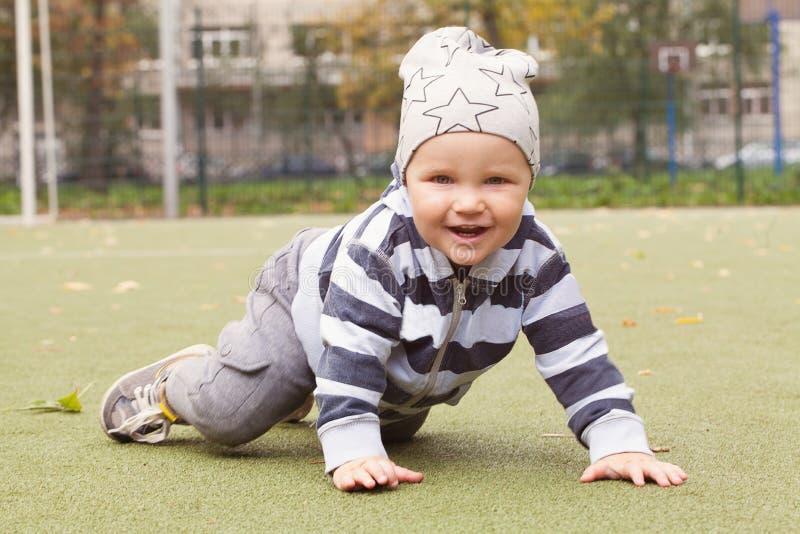 Усмехаясь ребенок играя outdoors, мальчик 1-2 года старых стоковое фото rf