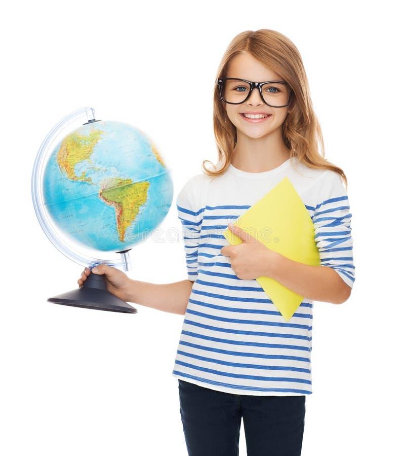Усмехаясь ребенок с глобусом, тетрадью и eyeglasses стоковые фотографии rf