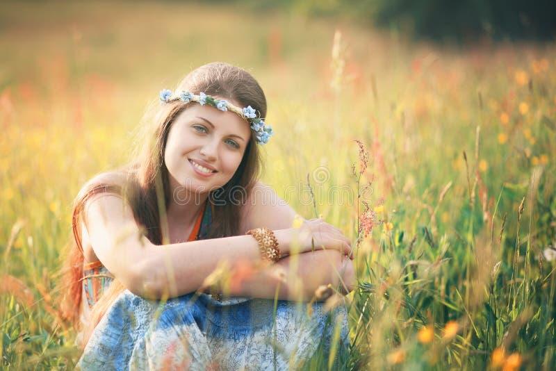 Усмехаясь романтичная женщина в луге цветка стоковое изображение rf