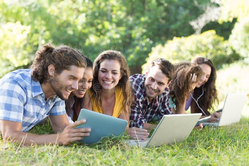 Усмехаясь друзья в парке используя ПК и компьтер-книжку таблетки стоковые фото
