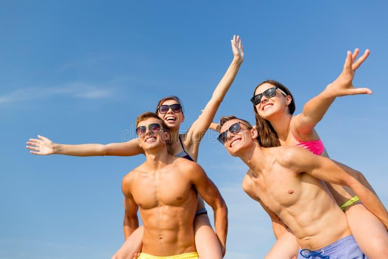 Усмехаясь друзья имея потеху на пляже лета стоковые фотографии rf