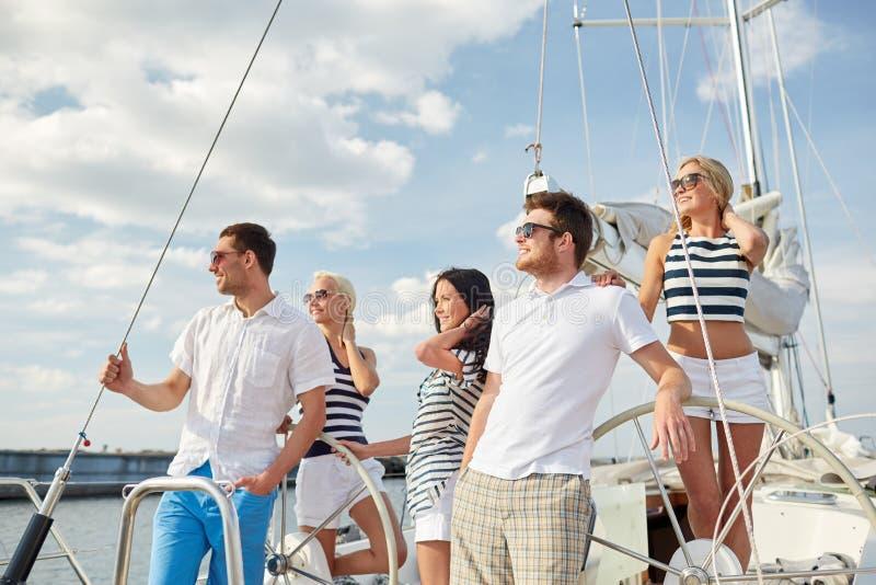 Усмехаясь друзья плавая на яхте стоковые изображения
