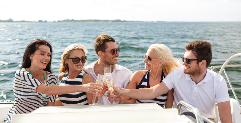 Усмехаясь друзья с стеклами шампанского на яхте стоковые изображения rf