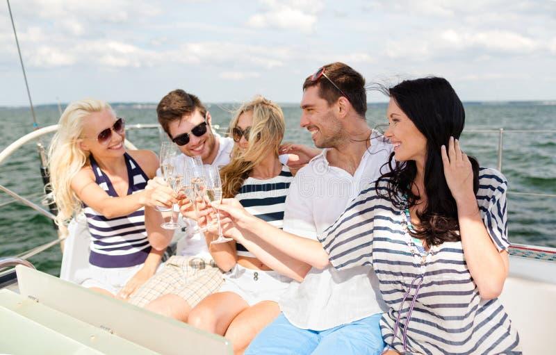 Усмехаясь друзья с стеклами шампанского на яхте стоковые фото