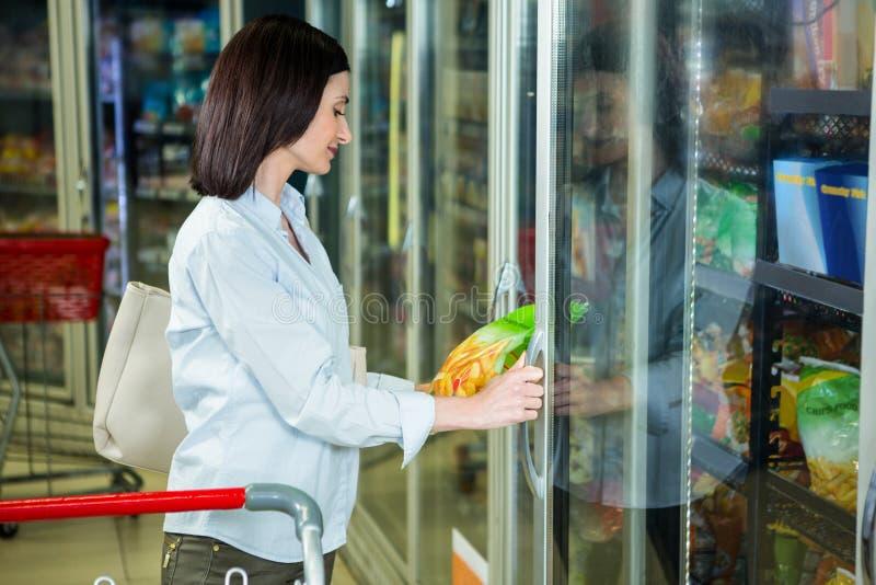 Усмехаясь рудоразборка женщины откалывает пакет в холодильнике стоковая фотография