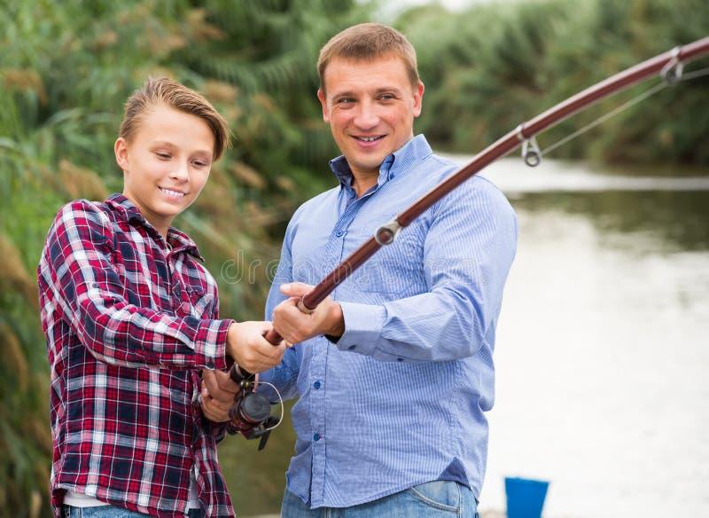 Усмехаясь рыбная ловля мальчика с человеком на пресноводном озере стоковое фото rf