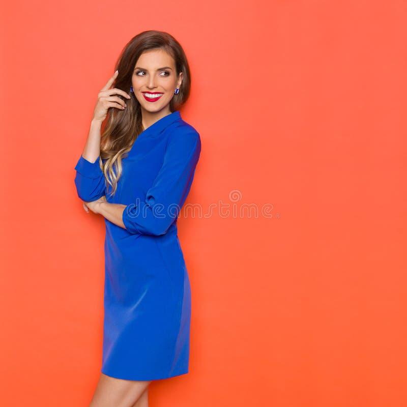 Усмехаясь сексуальная женщина в голубом мини платье рассматривает прочь плечо стоковое фото
