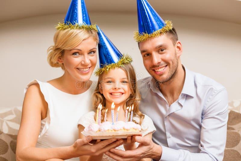 Усмехаясь семья в голубых шляпах с тортом стоковая фотография